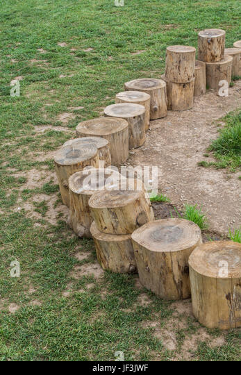 Log seating arranged round a campfire at an outdoor / environmental education centre for children (in Cornwall, - Stock Image