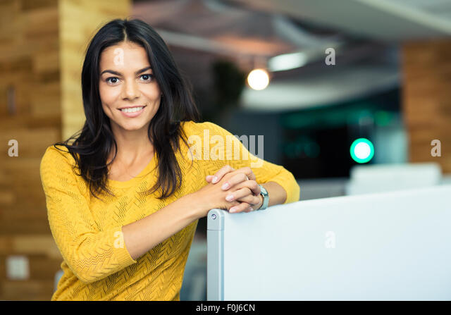 Portrait of a happy beautiful businesswoman standing in office and looking at camera - Stock Image