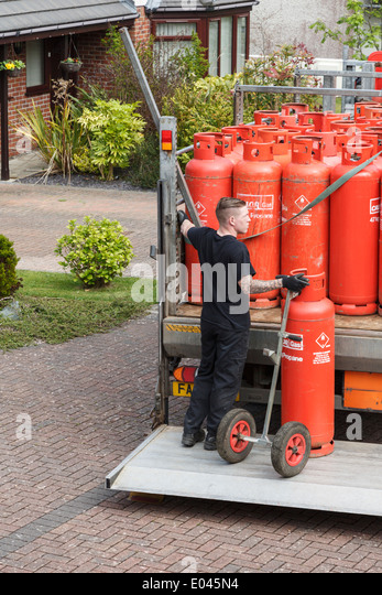 A delivery man delivering household red Calor Gas bottles on a pickup truck tail lift outside a house. North Wales, - Stock Image