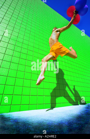 Male age 20-25 running and jumping with red balloons in his hand.The picture is shot against a vivid green tiled - Stock Image