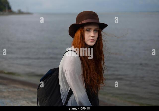 Serious Caucasian woman standing near ocean - Stock Image