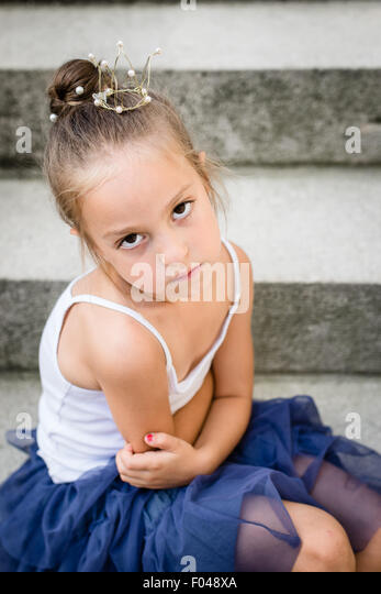 sad / bored / angry little princess with golden crown on her head. Selective focus. - Stock Image