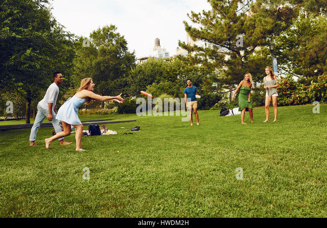 Five adult friends playing with flying disc in park - Stock-Bilder