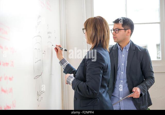 Business people writing on whiteboard in office - Stock-Bilder