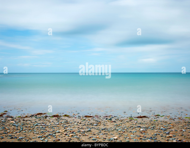 seascape photograph of church bay Anglesey Wales, long exposure in daylight giving movement in the sky and sea with - Stock-Bilder