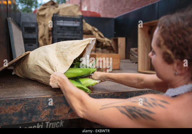 Stall holder unloading sacks of organic food for store - Stock Image