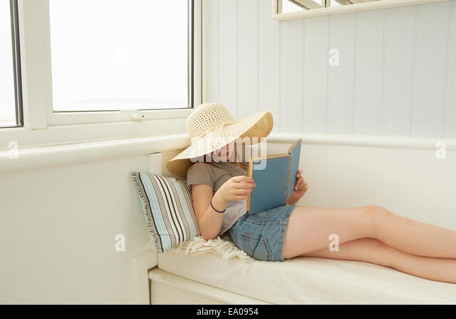 Girl in sunhat reading on holiday apartment porch seat - Stock Image