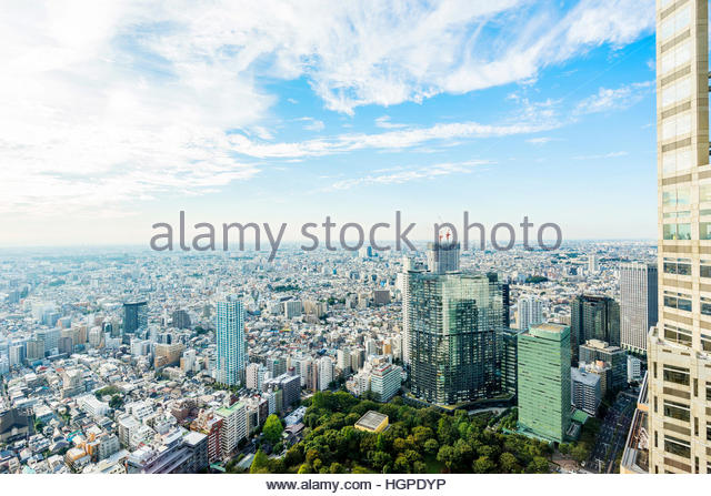 Business and culture concept - panoramic modern city skyline bird eye aerial view under sun and blue cloudy sky - Stock Image