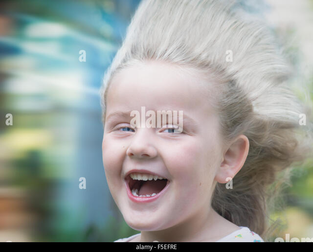 Portrait of a girl with hair blowing in wind - Stock Image