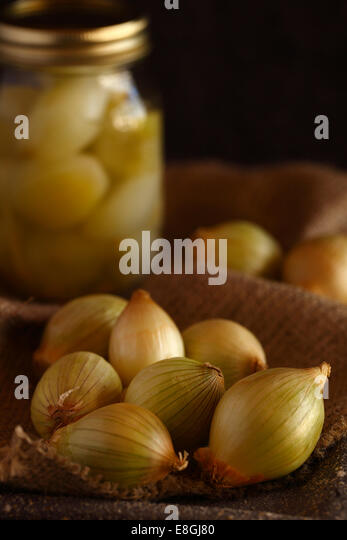 Onions and a jar of pickled onions - Stock Image