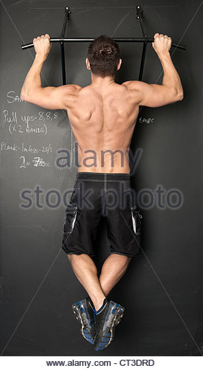 Man doing pull ups in gym - Stock Image