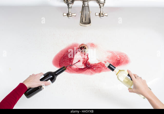 Detail of a couple pouring away wine in an act of giving up alcohol - Stock-Bilder