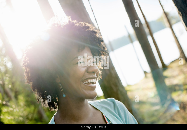 A young woman with curly black hair in the shade of trees by a lake shore - Stock Image