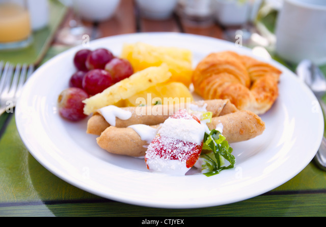 Fruit Crepe And Croissant On A White Plate; Puerto Vallarta, Mexico - Stock-Bilder