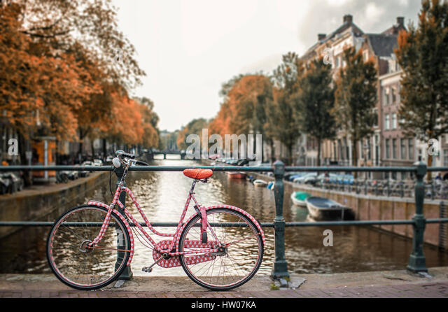 Bicycles parked on a bridge in Amsterdam at sunset, The Netherlands - Stock Image