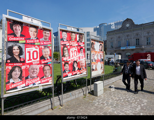 Two men walking past European election posters on place Luxembourg square in the EU district of Brussels, Belgium - Stock Image