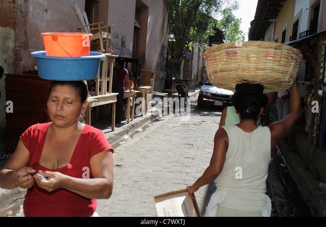 Nicaragua Granada Calle Atravesada shopping market furniture for sale sidewalk Hispanic woman carrying on head basket - Stock Image