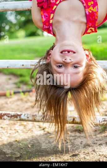 girl missing teeth upside down - Stock Image