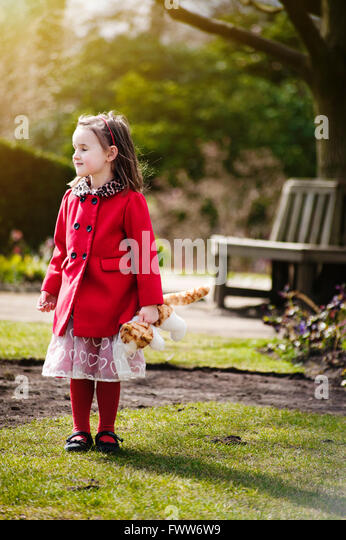 a lost small girl wearing red coat standing in park holding a toy - Stock Image