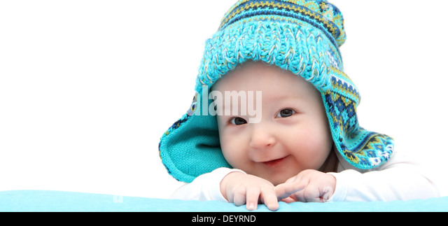 happy baby boy in knitted hat on stomach - Stock Image