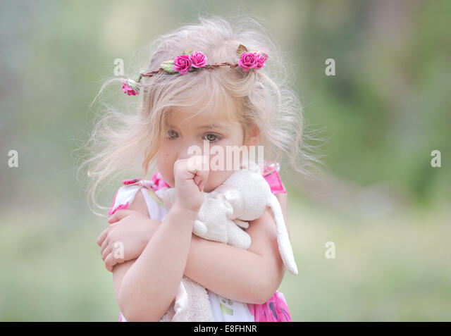 USA, Little girl (4-5) sucking thumb and clutching soft toy outdoors - Stock Image