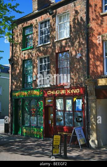 A tattoo studio and money lending shops on High Street, Taunton, Somerset, England, UK - Stock Image