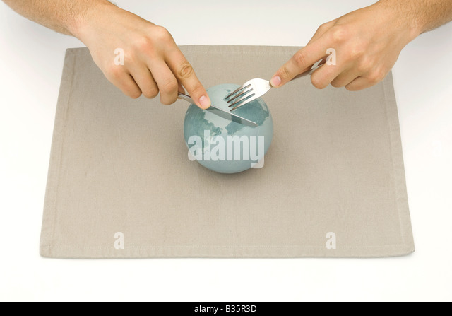 Globe resting on placemat, hands using knife and fork to cut up globe - Stock-Bilder