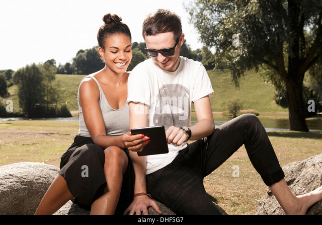 Young couple using digital tablet in park - Stock-Bilder