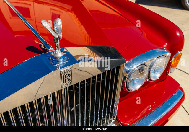 Parked older red Rolls Royce automobile, a symbol of wealth. - Stock Image