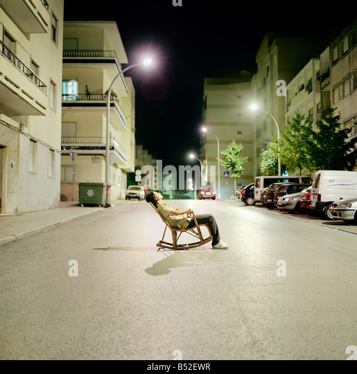 Young man sitting in a rocking chair in the middle of a road Setubal Portugal - Stock-Bilder