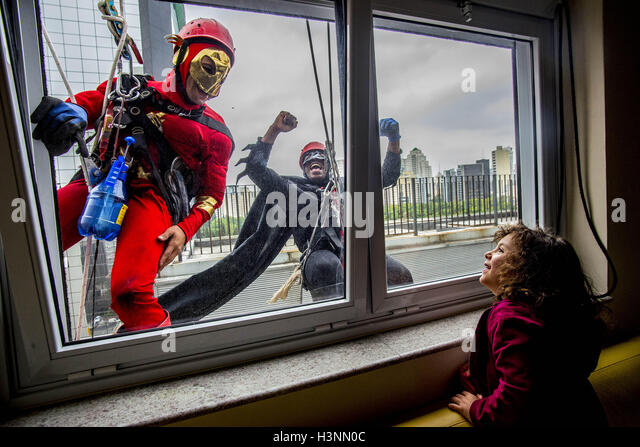 Sao Paulo, Brazil. 11th Oct, 2016. Men dressed as comic book heroes, Batman and The Flash, prepare to clean the - Stock Image