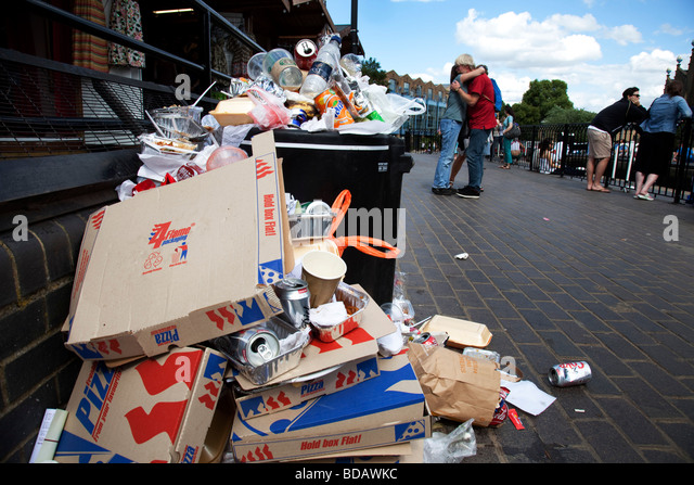 Litter overflows a bin at Camden in North London. Rubbish due to crowds builds throughout the day. A trash mountain - Stock Image