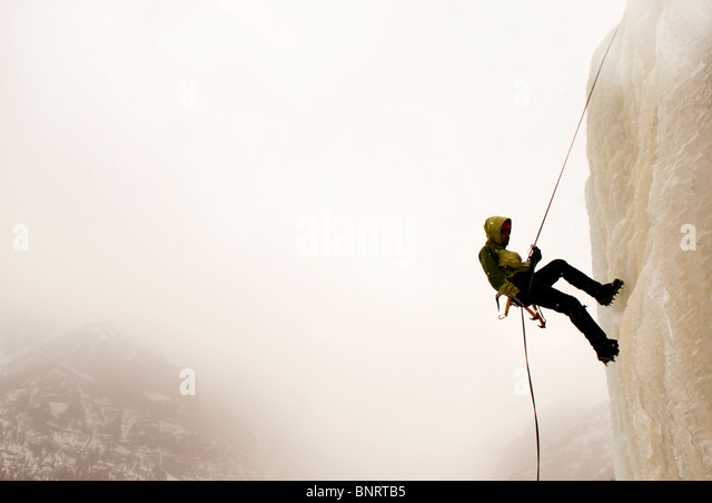 A man ice climbing. - Stock Image