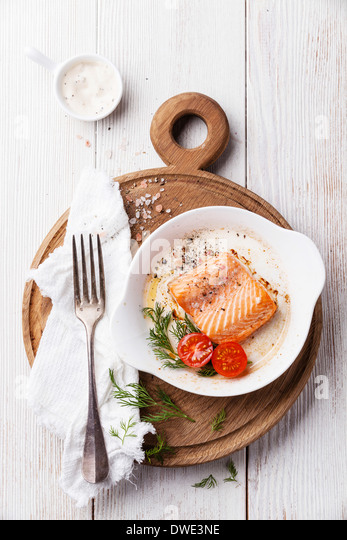 Baked salmon in a bowl on a wooden board - Stock Image
