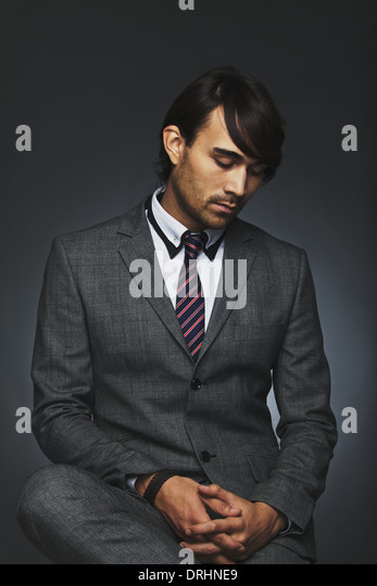 Thinking young business man sitting against black background. Young male entrepreneur looking down in thought. Mixed - Stock-Bilder