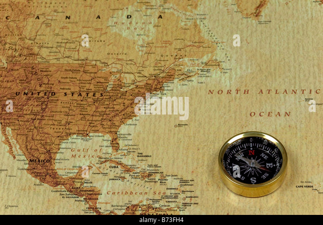A brss compass on an old map showing the North Atlantic ocean and the United States of America - Stock Image