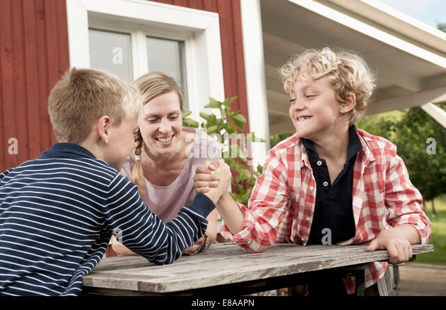 Two young boys arm wrestling mother watching - Stock Image