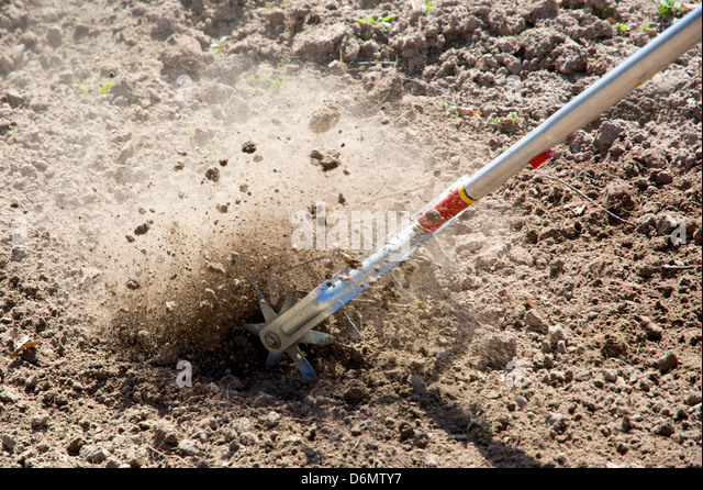Loosening the soil in a garden with a manual rotary cultivator. - Stock Image