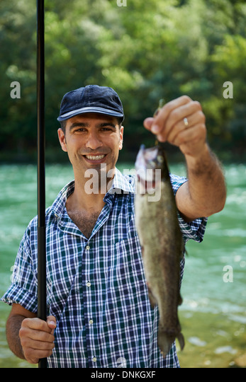 mid adult fisherman on holidays on river, relaxing and fishing trout. Focus on background - Stock-Bilder