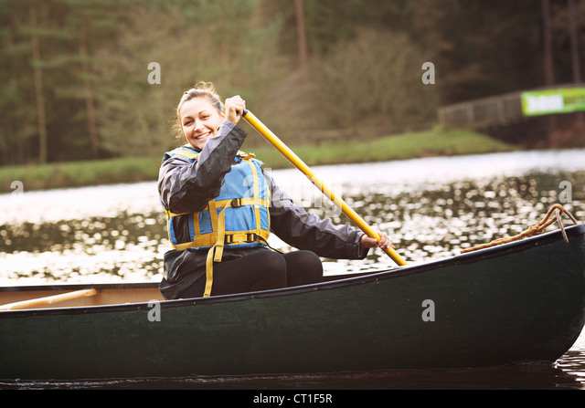 Woman rowing canoe on still lake - Stock Image