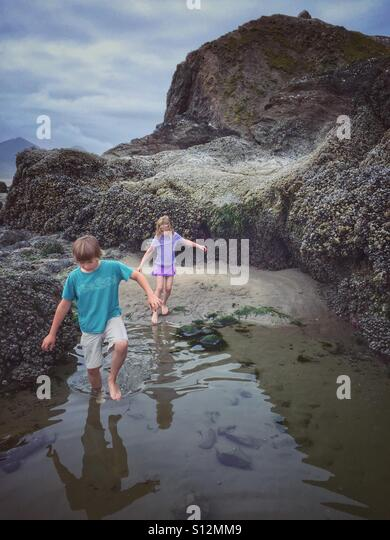 Two children explore the shallows off the Oregon coast. - Stock Image