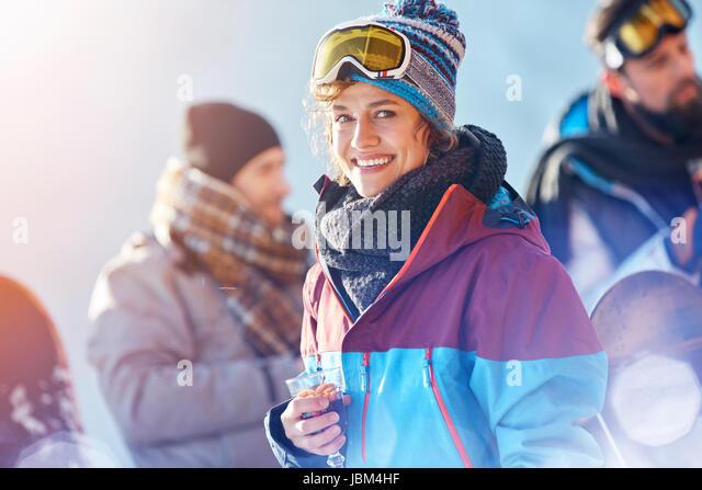 Portrait smiling female skier drinking cocktail - Stock-Bilder