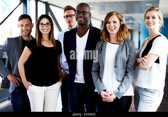 Group of young executives standing, smiling at camera and posing for picture - Stock Image