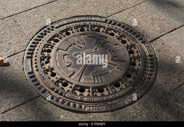 A man hole cover in the pavement of K damm Berlin. it shows some of the most famous sights in Berlin. - Stock-Bilder