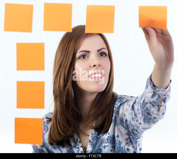Young lady attaches sticker to the board - Stock Image