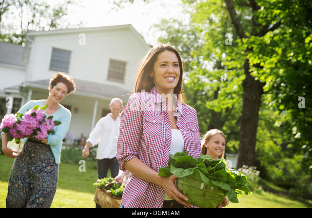 Family party. Parents and children carrying flowers, fresh picked vegetables and fruits. Preparing for a party. - Stock Image