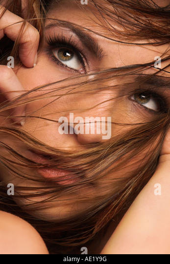 A young brunette woman looking off with her hair blowing in front of her face. - Stock Image