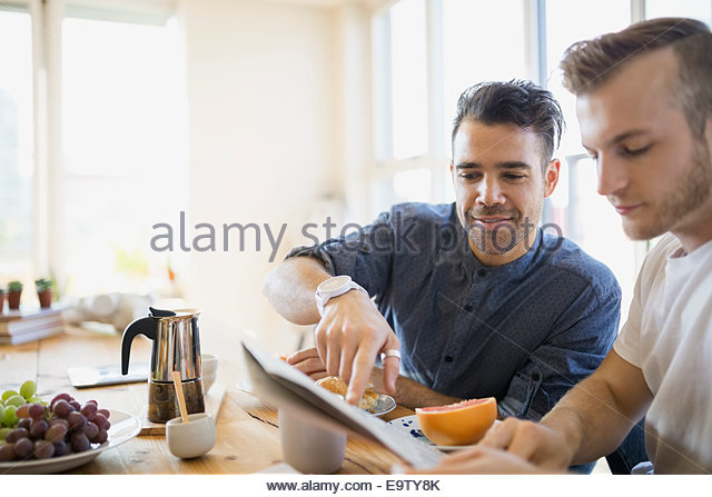 Homosexual couple reading newspaper and enjoying breakfast - Stock Image