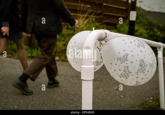 A pair of white 'Just Married' ballons tied to a railing on the walk back from the church - Falmouth, Cornwall. - Stock Image