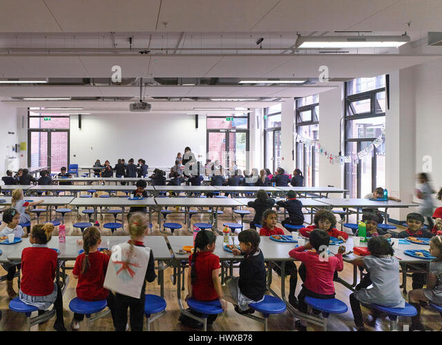 Lunch time in dining hall. Wembley High Technology College Primary, North Wembley, United Kingdom. Architect: Curl - Stock-Bilder